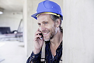 Smiling worker on construction site on cell phone - FMKF001679