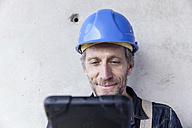 Smiling man wearing hard hat looking at digital tablet - FMKF001682