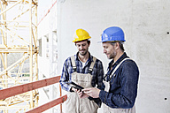 Two construction workers on construction site looking at digital tablet - FMKF001732