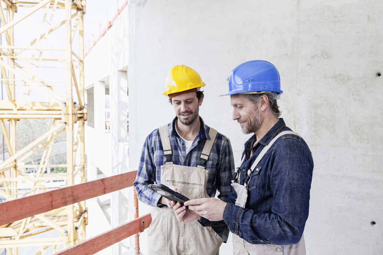 Two construction workers on construction site looking at digital tablet - FMKF001732 - Jo Kirchherr/Westend61