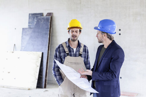 Construction worker and architect with plan talking on construction site - FMKF001686