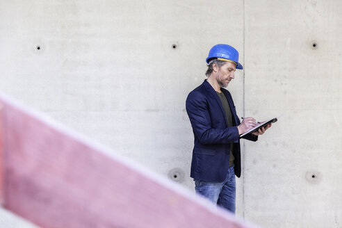 Architect on construction site writing - FMKF001689