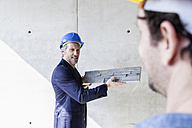 Architect showing sample on construction site - FMKF001692