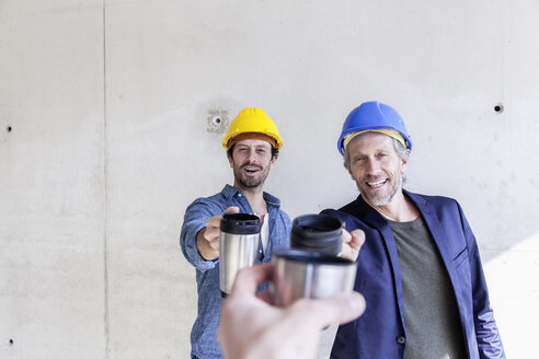 Two happy men on construction site toasting with mugs - FMKF001844