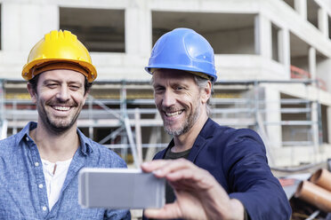 Two happy men on construction site taking a selfie - FMKF001700