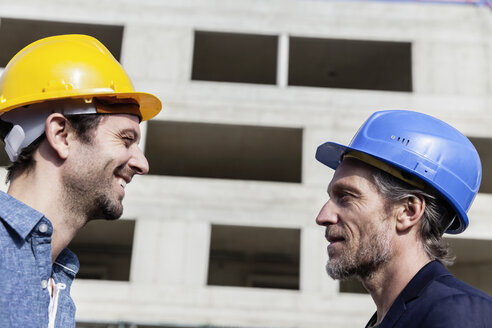 Two men on construction site wearing hard hats - FMKF001706