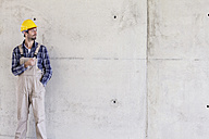 Man with hard hat on construction site at concrete wall - FMKF001709