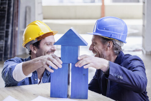 Two happy men with hard hats and model house - FMKF001721