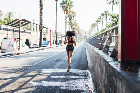 Spain, Barcelona, back view of jogging young woman on a street - EBSF000710