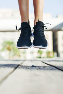 Sportive young woman wearing black sneakers jumping in the air, close-up - EBSF000713