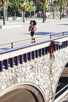 Spain, Barcelona, jogging young woman in the city - EBSF000718