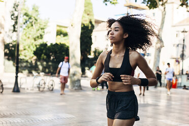 Spain, Barcelona, jogging young woman in the city - EBSF000748