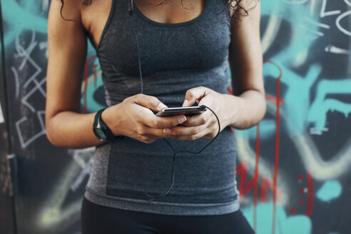 Young woman holding smartphone hearing music with earphones, close-up - EBSF000753
