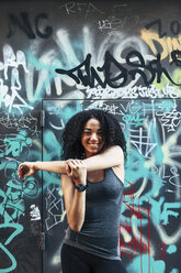 Portrait of smiling young woman standing in front of graffiti wall - EBSF000754