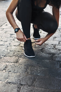 Sportive young woman tying her shoe on pavement - EBSF000757