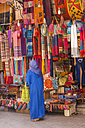 Morocco, Marrakesh, woman in traditional cloth in front of a shop - JUN000335