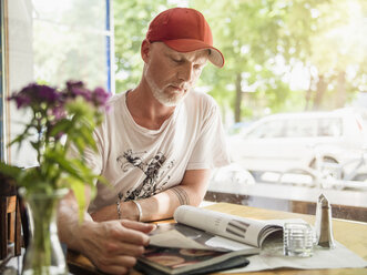 Germany, Berlin, Mature man sitting in cafe, reading magazines - TAM000228