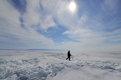 Russia, Lake Baikal, man walking on frozen lake - GNF001352