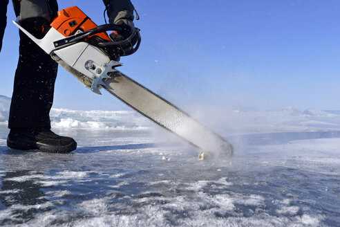 Russia, Lake Baikal, man opening an ice hole with a motor saw for ice diving - GNF001337