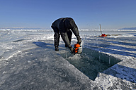 Russia, Lake Baikal, man opening an ice hole with a motor saw for ice diving - GN001338