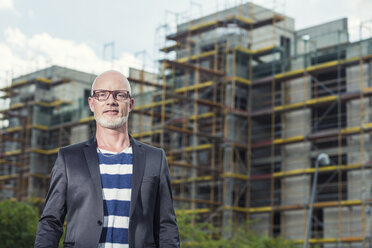 Portrait of a man standing in front of construction site - TAM000227