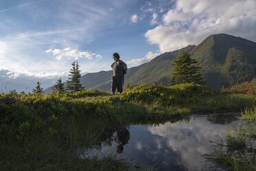 Austria, Tyrol, hiker in mountainscape looking at view - MKFF000221
