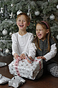 Brother and sister sitting with Christmas presents in front of Christmas tree - LBF001138