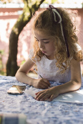 Spain, little girl drawing a picture that she is seeing on a smartphone - RAEF000231