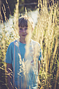 Little boy standing on a meadow at backlight - SARF002023