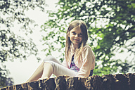Portrait of little girl sitting on big tree trunk - SARF002028