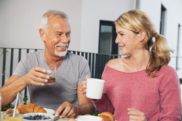 Father and adult daughter having  breakfast on balcony - MFF001703