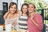 Two women and a girl at breakfast table on balcony - MFF001705