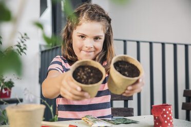 Little girl showing flowerpots with  seeds and soil on the balcony - MFF001720