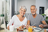 Elderly couple having breakfast at balcony - MFF001734