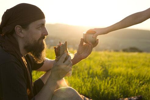 Germany, man on a meadow having breakfast at sunrise - MIDF000495