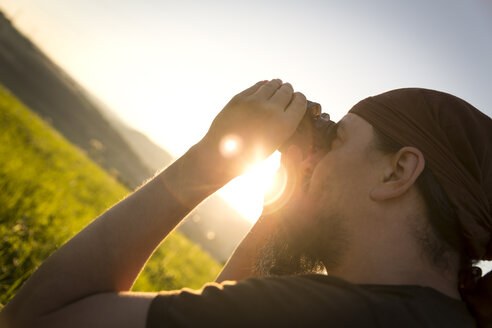 Germany, man looking through binocular at sunrise - MIDF000498