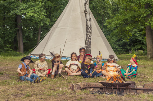 Germany, Saxony, Indians and cowboy party, Children sitting at bonfire - MJF001653