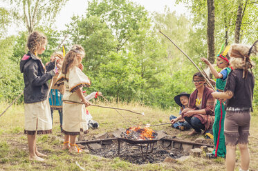 Germany, Saxony, Indians and cowboy party, Children rasting marshmallows on sticks - MJF001677