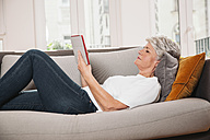 Mature woman relaxing with digital tablet on a couch at living room - MFF001693