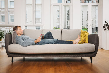 Man relaxing with digital tablet on a couch at living room - MFF001748