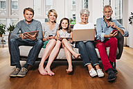 Group picture of three generations family with different digital devices sitting on one couch - MFF001695