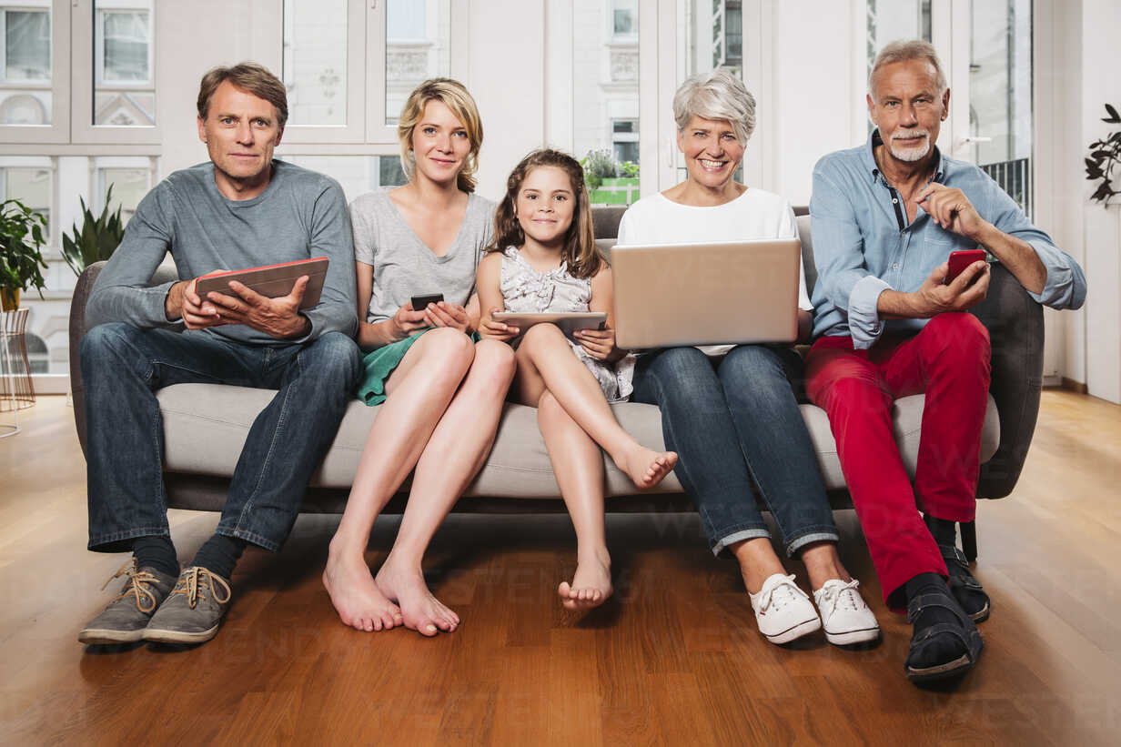 Group picture of three generations family with different digital devices sitting on one couch - MFF001695 - Mareen Fischinger/Westend61
