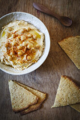 Bowl of Hummus and flat bread on wood - EVGF002178