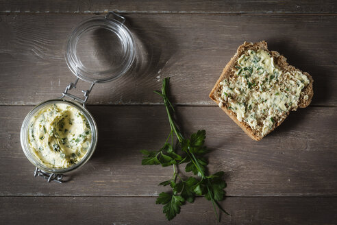 Herb butter, slice of spelt bread on wood - EVGF001899