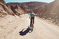 Chile, Man riding a mountain bike through the Valle de la Muerte, Atacama Desert - GEMF000263