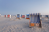 Germany, North Sea, wicker chairs on the beachfront in the evening - MEMF000824