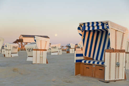 Germany, North Sea, wicker chairs on the beachfront in the evening - MEMF000825