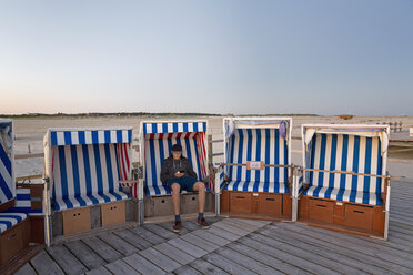 Germany, St Peter-Ording, teenage boy with smartphone sitting in hooded beach chair - MEMF000828