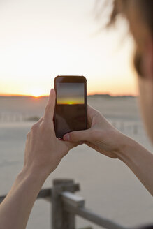Teenage boy taking picture of sunrise with his smartphone - MEMF000835