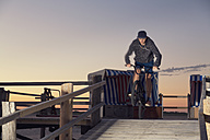 Germany, St Peter-Ording, teenager jumping with his BMX bike on wooden ramp - MEMF000836